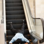 Fallen man at base of an escalator